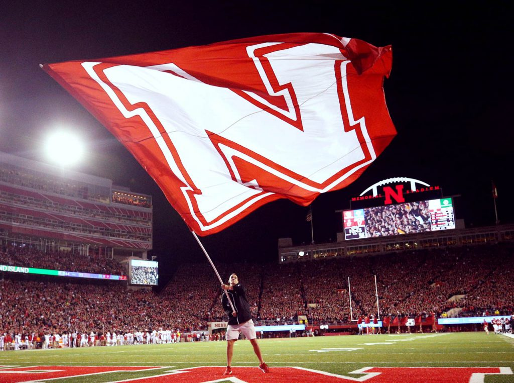 Grant Carstens waves the Nebraska flag after the Huskers score a touchdown against Wisconsin in the third quarter Saturday night at Memorial Stadium. (Independent/Andrew Carpenean)