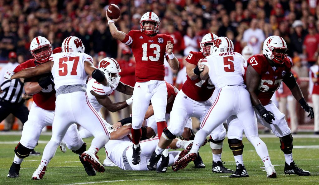 Nebraska quarterback Tanner Lee throws amongst Wisconsin players and Huskers teammates Saturday night at Memorial Stadium.
