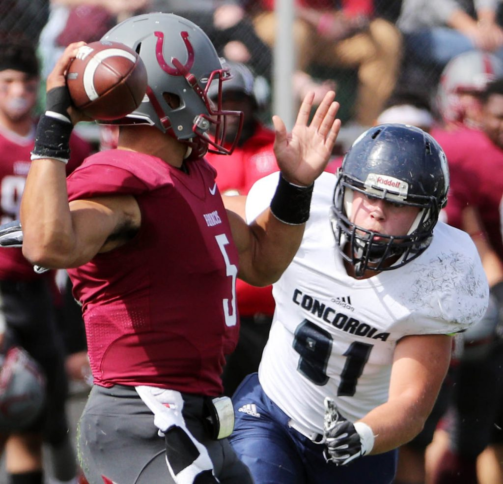 Hastings College quarterback Anthony Cloyd is pressured by Concordia defensive lineman Aaron Rudloff.