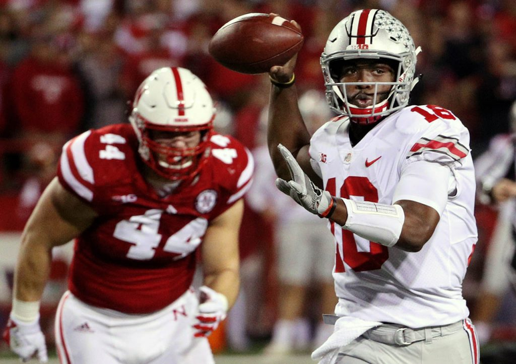 Ohio State quarterback J.T. Barrett throws on the run with Nebraska's defensive lineman Mick Stoltenberg trailing behind Saturday night at Memorial Stadium. (Independent/Andrew Carpenean)