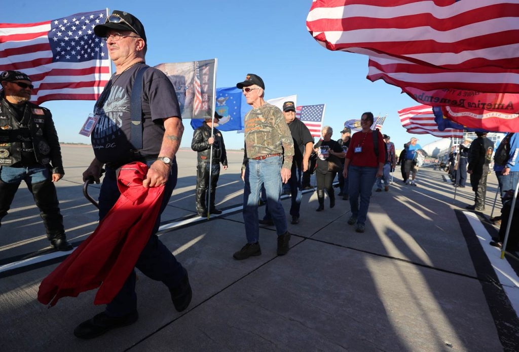 Veterans walk by Patriot Guard Riders posting two lines of American flags during a Hero Flight Welcome Home Wednesday at the Central Nebraska Regional Airport.