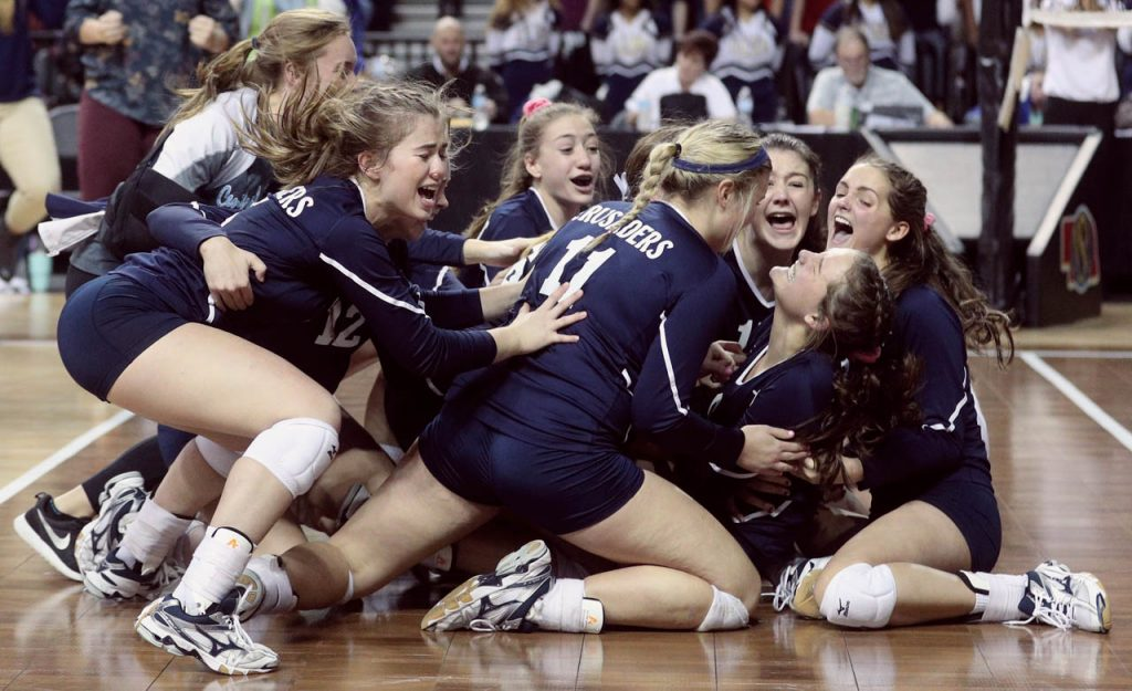 Grand Island Central Catholic volleyball players make a dogpile while celebrating their victory over Lincoln Lutheran at Pinnacle Bank Arena. The Crusaders advance to play Wahoo in the Class C1 championship game.