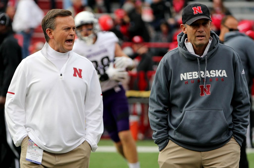 Billy Devaney, left, talks with Nebraska head coach Mike Reily during pregame preparations against Northwestern.