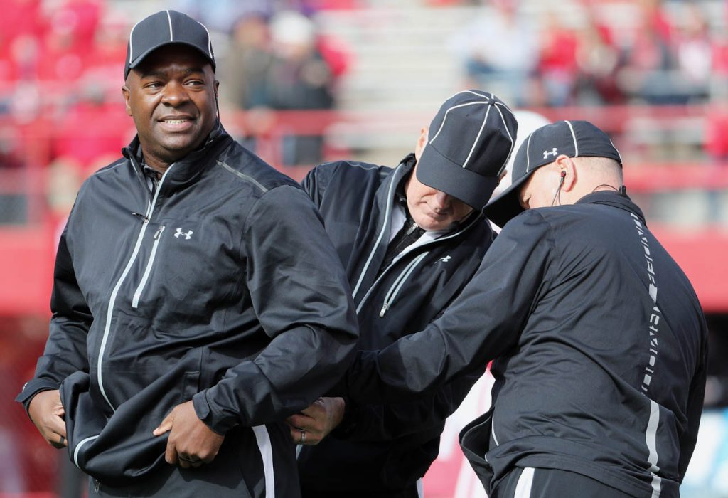 Big 10 referee Mike Brown, left, gets a helping hand from other refs while preparing for the Nebraska vs. Northwestern football game at Memorial Stadium in Lincoln, Neb.