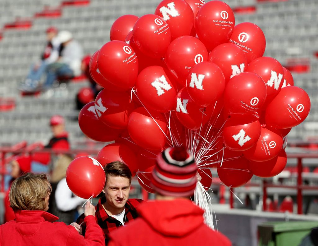 Glen Ready, a recent University of Nebraska graduate, hands out balloons to fans prior to the Nebraska vs. Northwestern football game at Memorial Stadium in Lincoln, Neb.