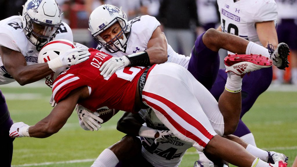 Northwestern cornerback Alonzo Mayo hops on top of Huskers running back Devine Ozigbo for a tackle.