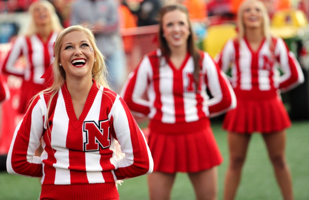 Nebraska cheerleaders laugh while watching a video screen as Huskers football players try to guess the name of the late musical artist John Denver singing Thank God I'm a Country Boy.