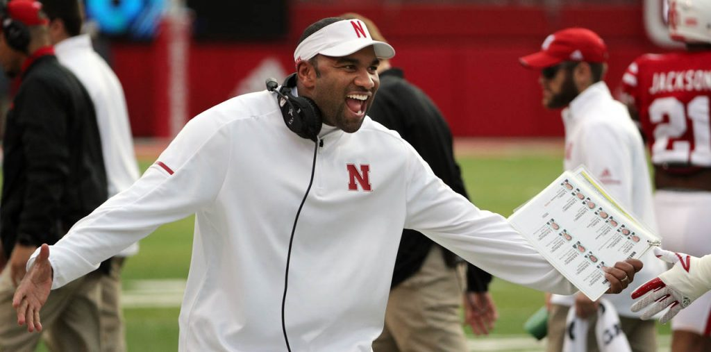 Nebraska cornerback coach Donte Williams congratulates defensive players after making a big play against Northwestern at Memorial Stadium Saturday.