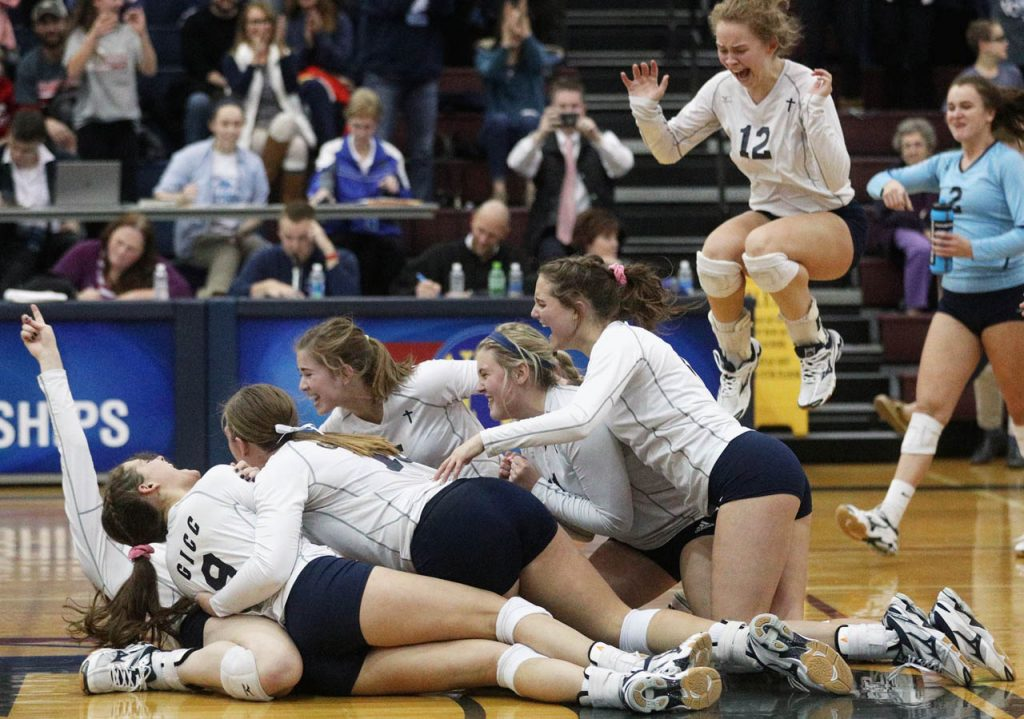 The Grand Island Central Catholic Crusaders volleyball team celebrates their Class C1 victory over Concordia in four sets at Thursday at Lincoln North Star High School.