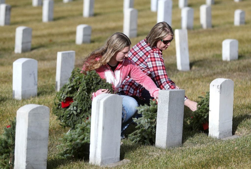 Brianna and Nicki Mowrey places wreaths at the headstones of veterans buried at the Grand Island Veterans Cemetery.