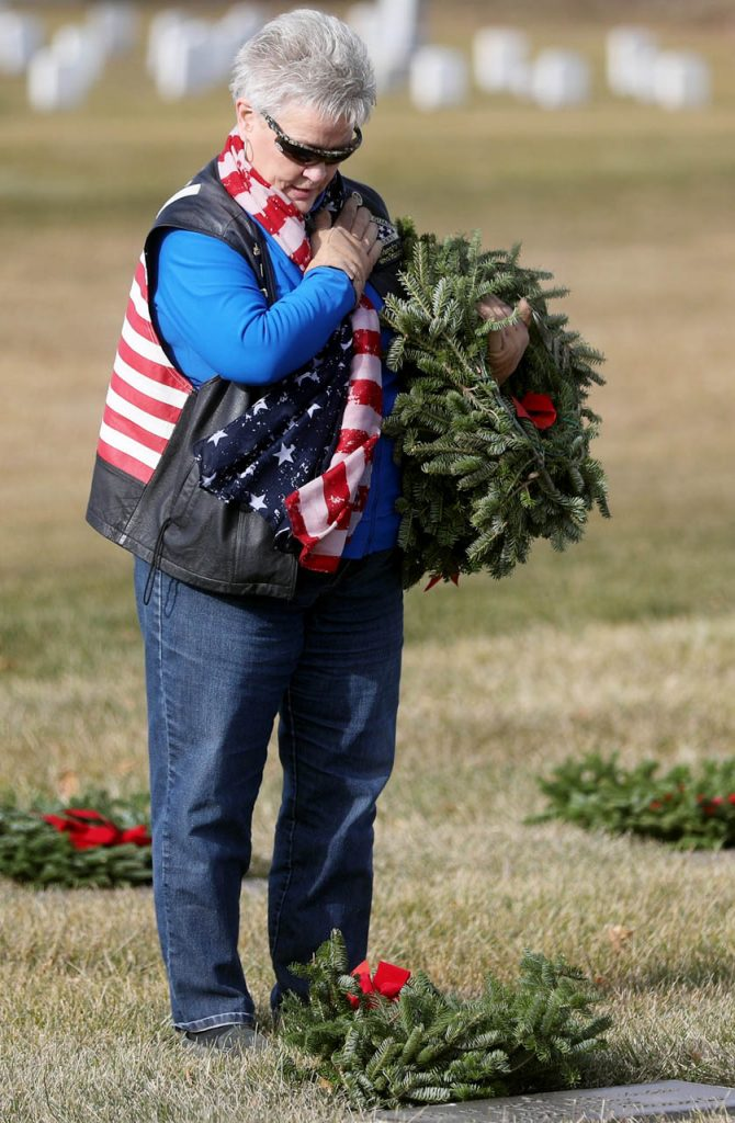 Billy Rayburn of Kearney places her hand over her heart while reading the name of a veteran after placing a wreath on a gravesite buried at the Grand Island Veterans Cemetery Saturday. Rayburn is flag captain of the Patriot Guard Riders.