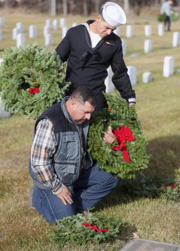 Elias Terrazas Sr. (kneeling) reads the name of a veteran as his son U.S. Navy construction man Elias Terrazas Jr. holds extra wreaths at the Grand Island Veterans Cemetery.
