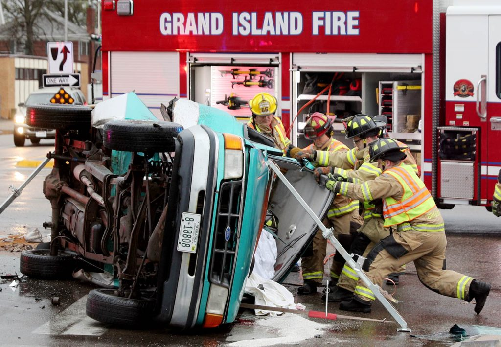 Grand Island firefighters pull back on the cab of a Ford truck to remove an occupant involved in a motor vehicle accident on a rainy Friday morning at the intersection of 2nd and N. Eddy Streets.