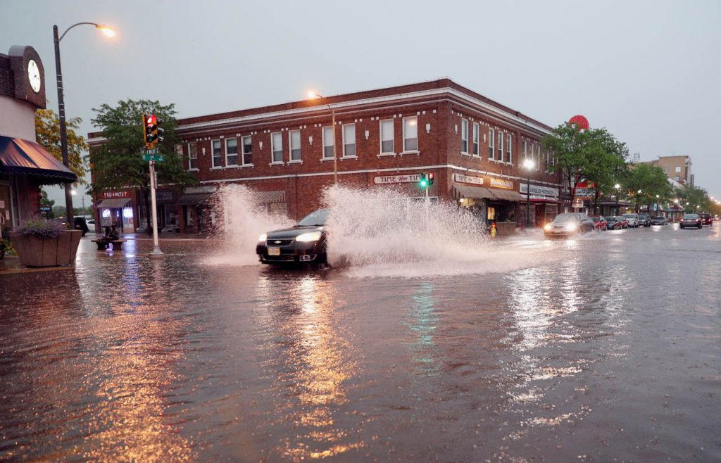 Motorists drive through deep water on a second straight night of severe thunderstorms moving through the region creating flooding at the intersection of 3rd and Walnut Streets in downtown Grand Island.