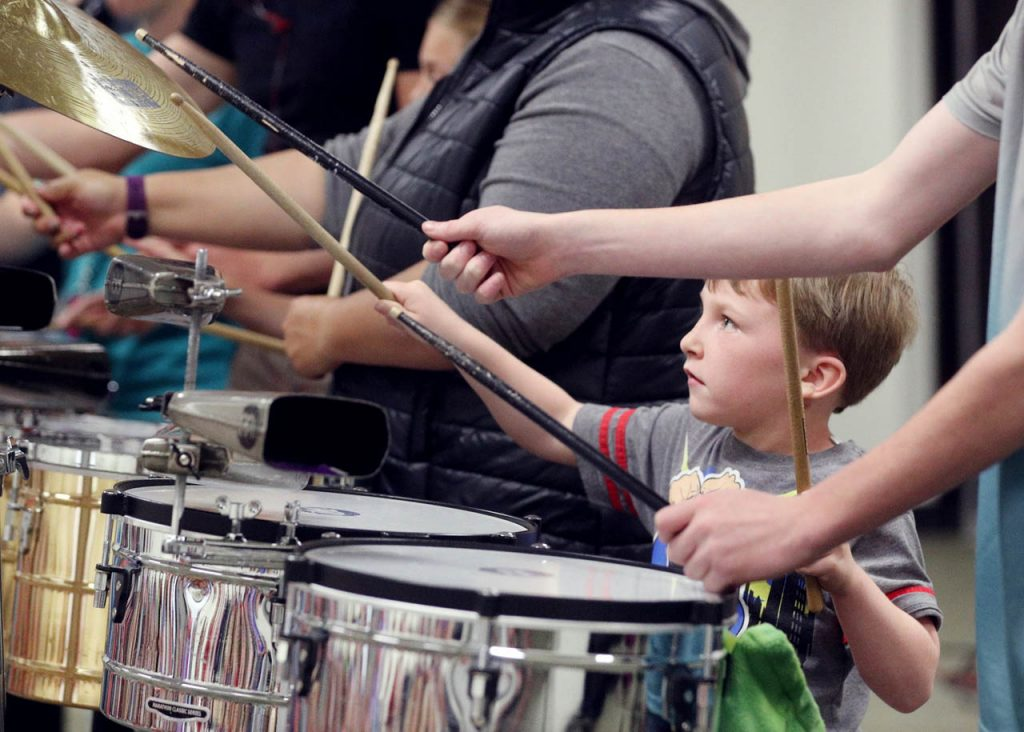 RyeLee O'Brien with YWCA childcare learns to play drums with Sheltered Reality musical drum group during The Children's Summer Reading Program Friday at the Grand Island Library.