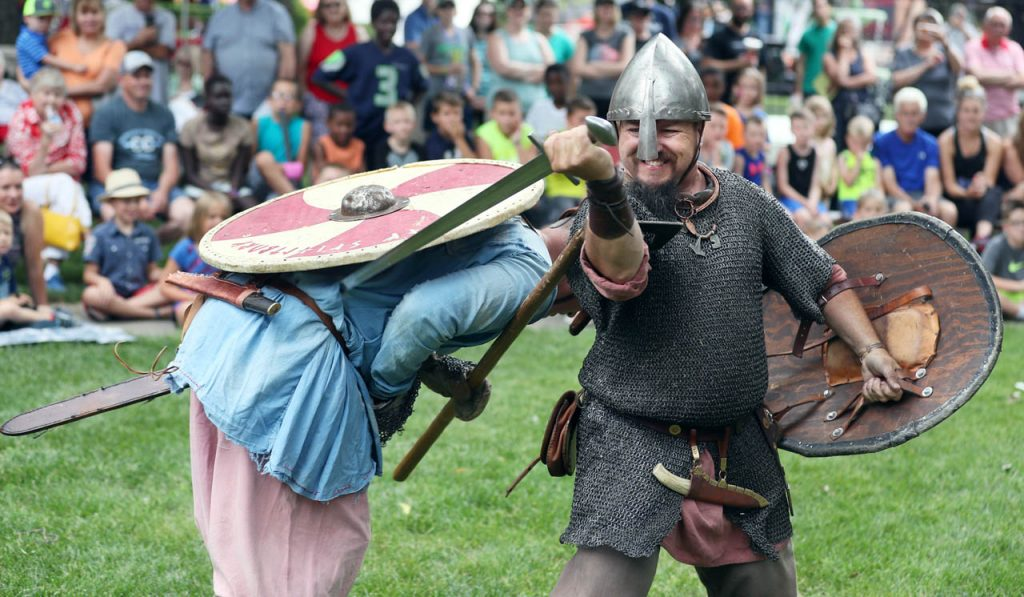 Philip Ryan, right, slashes Ryan Carlson as the two have a sword fight during a Skjaldborg Vikings reenactment in the first of three performances during the 65th annual Swedish Midsommar Festival in Stromburg Saturday.