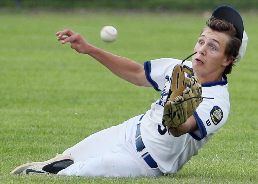Five Points Bank centerfielder Keyin Wentling charges up on a shallow pop up to make a sliding catch against Hastings Runza at Ryder Park Friday.