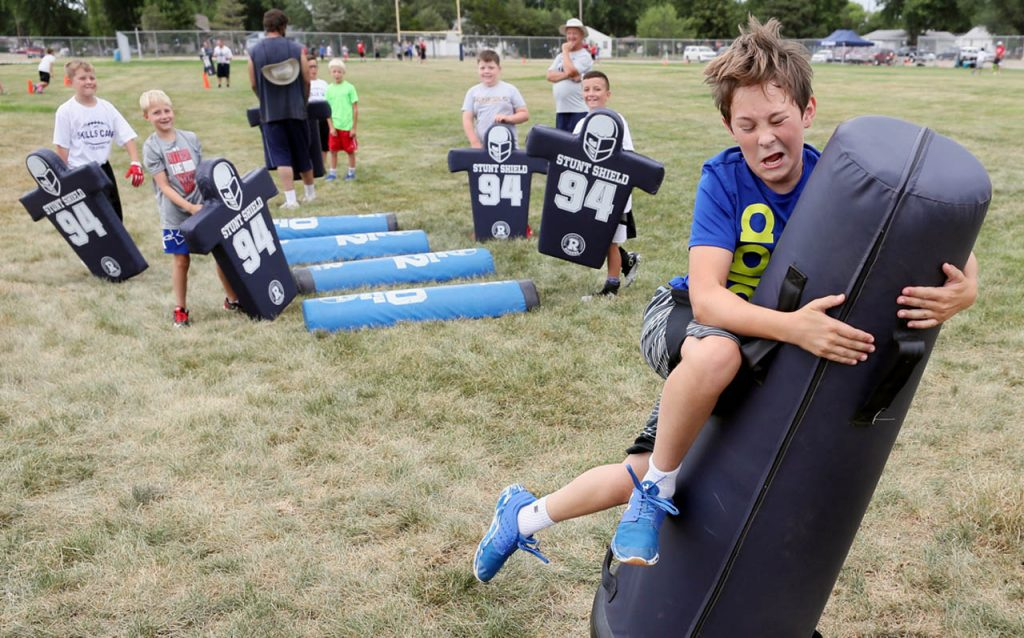 George Pilsl takes down a pop-up dummy as the last part of a football agility drill during Junior Skills Camp Central for fourth through eighth-graders Friday at the Grand Island Central Catholic practice field.