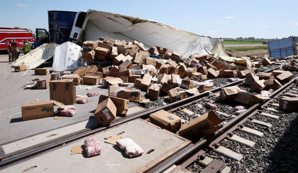 Boxes of pork are strewn across railroad tracks after a tractor trailer of a semi driven by Anton Kristijanto of Dakota, Neb. was struck at a train crossing on Hwy. 30 and 5th Road west of Chapman Friday afternoon. Motorists were being diverted off Hwy. 30 onto 5th Rd. because of an accident blocking traffic.