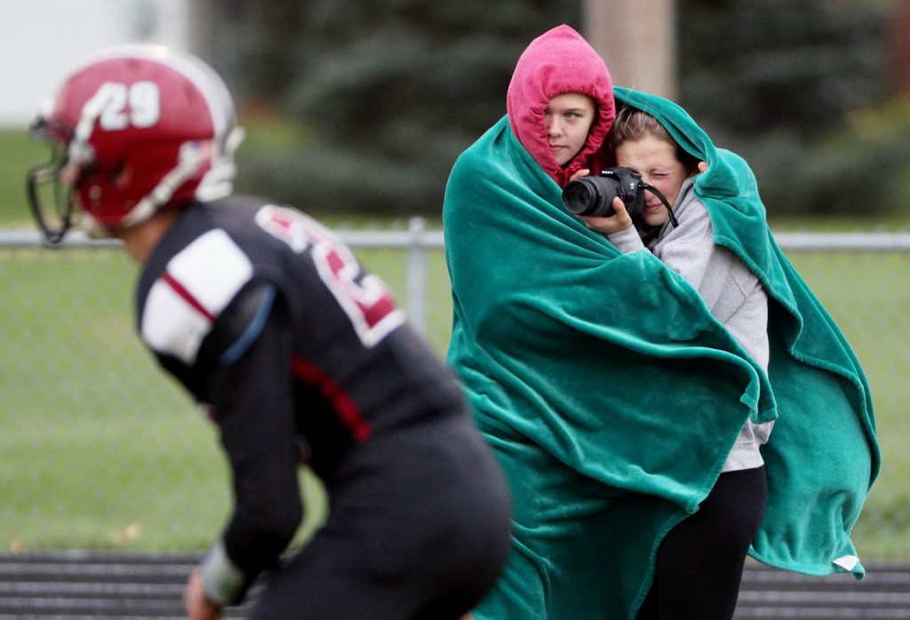 Johnson-Brock student Logan Edwards shields her classmate Hailee Sandfort from the cold wind as she takes photos of an 8-man playoff football game against Heartland Thursday night in Henderson.