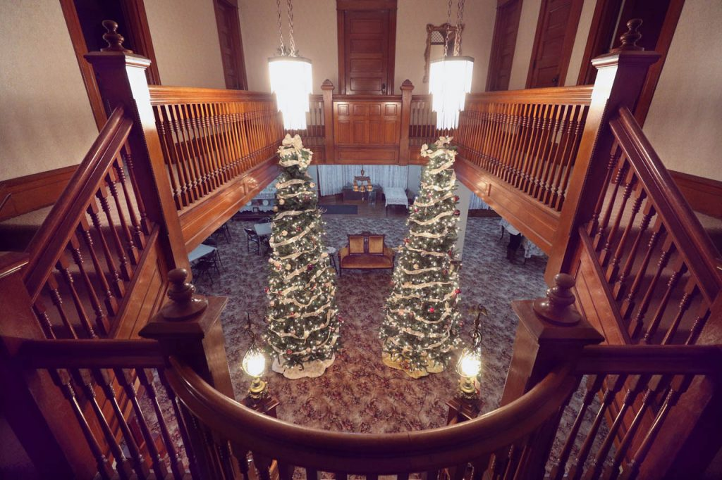 A look over a banister under chandeliers are two tall trees decorated by Grand Island Women's Club members inside the Hargis Mansion. The Andrew M. Hargis house built in 1898 is one of two stops on during the Holiday Tour of Homes.