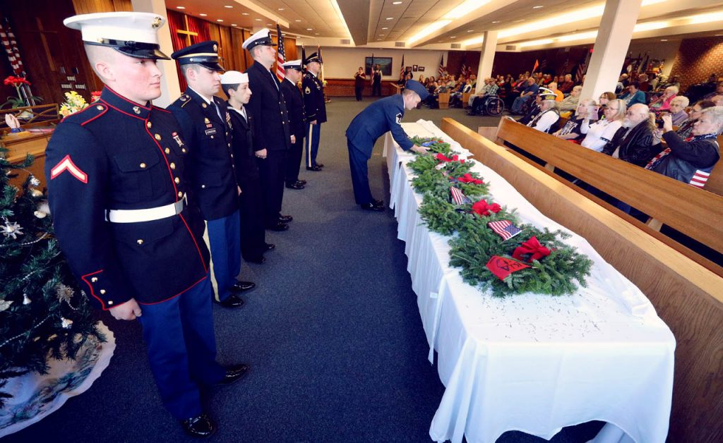 Sgt. Mike Evans with the USAF uses both hands during a presentation of wreaths at a Wreaths across America ceremony at All Faiths Chapel inside the Grand Island Veterans Home.